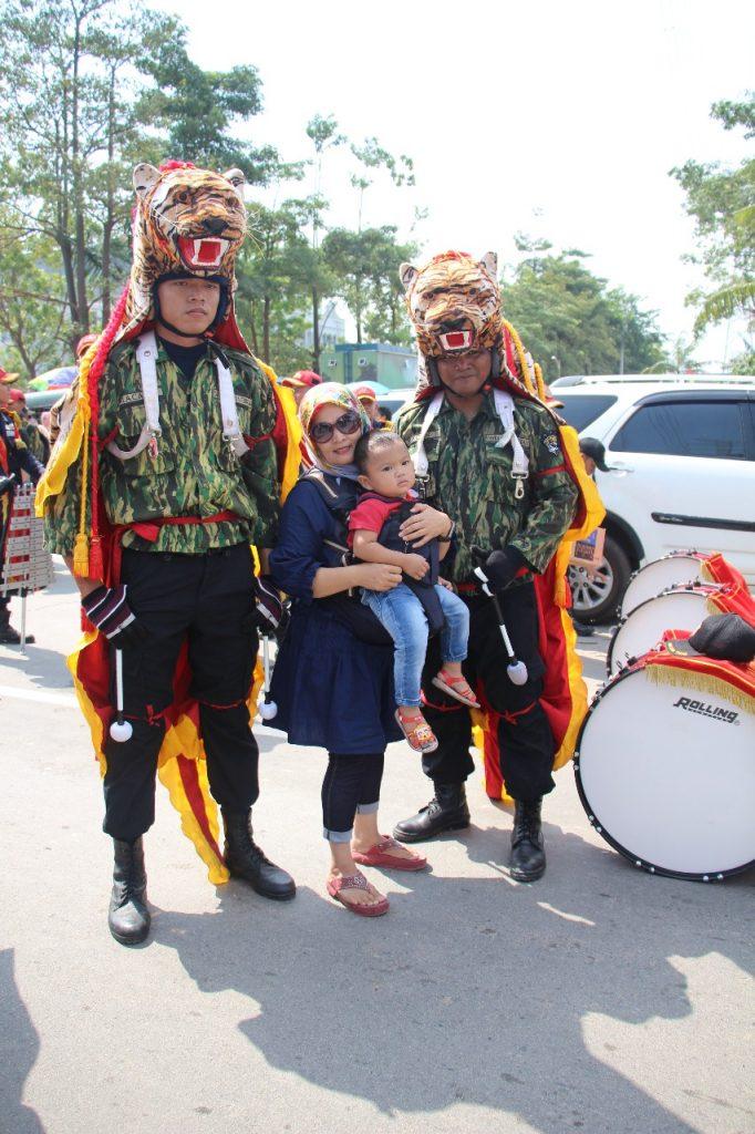 Ibu dan anak berfoto bersama personel Drumband saat pawai Kebudayaan